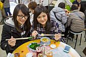 Two teenage girls enjoying lunch at Mak's Noodle Restaurant, Central, Hong Kong Island, Hong Kong