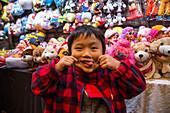 Young boy pulling a grimace, funny face at Temple Street Night Market, Tsim Sha Tsui, Kowloon, Hong Kong