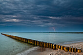 Groynes on the beach in the evening, thunder storm with lightning flash in the distance, Zingst, Darss, Baltic Sea, Mecklenburg-Vorpommern, Germany