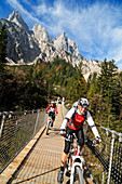 Mountain bikers passing chain bridge crossing Klausbach valley, Muehlsturzhoerner in background, Ramsua, Berchtesgadener Land, Upper Bavaria, Germany