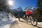 Mountain biker going uphill to Kuehroint alp, Berchtesgadener Land, Upper Bavaria, Germany
