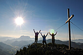 Female hikers cheering beside summit cross on mount Steinplatte, Waidring, Tyrol, Austria