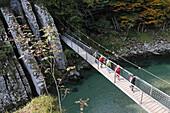 Female hikers passing a suspension bridge crossing Ache river at Klobenstein, Tyrol, Austria