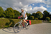 Woman riding a touring bicycle in Hofgarten, Munich, Upper Bavaria, Germany