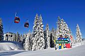 Skifahrer posieren an einem Schild, Skigebiet Winklmoosalm, Reit im Winkl, Chiemgau, Bayern, Deutschland