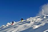 Zwei Skifahrer fahren ab, Skigebiet Steinplatte, Waidring, Tirol, Österreich