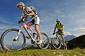 Mountain bikers passing Steiplatte, Lofer Mountains in background, Tyrol, Austria