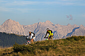 Mountain bikers passing Winklmoosalm, Berchtesgaden Alps in background, Chiemgau, Upper Bavaria, Germany