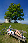 Female cyclists resting near a chapel, Toerwang, Samerberg, Upper Bavaria, Germany