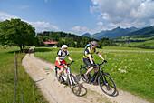 Couple riding e-bikes along a dirt track, Reit im Winkl, Chiemgau, Upper Bavaria, Germany