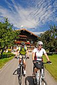 Couple riding e-bikes, Reit im Winkl, Chiemgau, Upper Bavaria, Germany