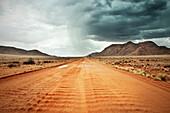 sandige rote Straße mit starkem Regen und Gewitter am Horizont, Tiras Gebirge, Tirasberge, Namib Naukluft Park, Namibia, Afrika