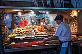 Cooks preparing steak and meat, Parilla type restaurant, Mercado del Puerto, Montevideo, Montevideo, Uruguay