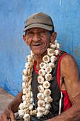 Man with garlic necklace at market, Santiago de Cuba, Santiago de Cuba, Cuba