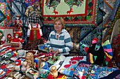 Woman offering Russian handicraft and souveniers on market, Uglich, Yaroslavl Oblast, Russia