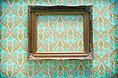 Golden frame, empty, hanging on a wall papered with 70´s paper