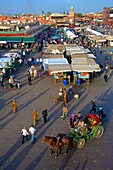 Restaurants, terraces, Kharbouch mosque and minaret, and tourists, Jemaa-el-Fna square, Marrakech, Morroco, North Africa.