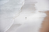 Person alone on beach, high angle