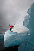 Mature woman climbing on iceberg, Jokulsa Loni, Iceland