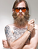 Portrait of young man with tattoos smoking cigarette