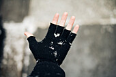 Person wearing fingerless glove in the snow