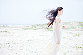 Young woman with long windswept black hair on beach