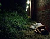 Woman lying by brick wall at night