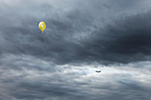 Yellow balloon floating toward cloudy sky