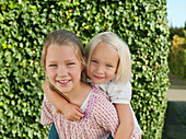 Girl carried by sister on back, smiling, portrait