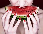 Woman biting slice of watermelon