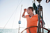 Young man steering yacht
