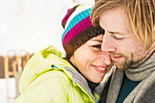Mid adult couple embracing, woman wearing knit hat