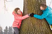 Mid adult couple hugging tree