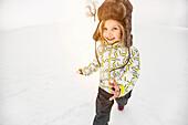 Girl wearing furry hat walking in snow