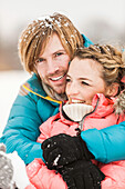 Mid adult couple embracing with snow in hair