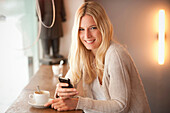 Portrait of young woman holding cellphone in cafe