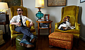 Young man and pet dog relaxing in armchair in living room