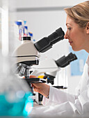 Female microbiologist viewing specimen under microscope in lab