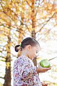 Child holding bitten green apple