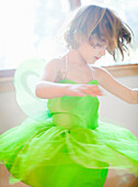 Child in green fairy costume dancing