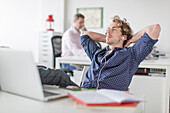 Young office worker reclining at desk with hands behind head