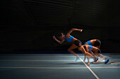 Female athlete running from starting block