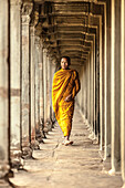 Young Buddhist monk walking through temple, Angkor Wat, Siem Reap, Cambodia