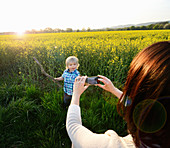 Mother photographing son on smartphone in field