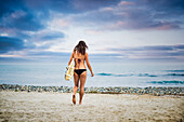 Young woman carrying surfboard to sea