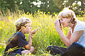 Woman taking photograph of boy blowing kiss