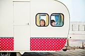 Boys looking through caravan windows, portrait