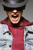 Young man wearing hat and shouting, studio shot