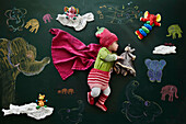 Baby girl sleeping against drawings on blackboard, overhead view