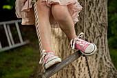 Cropped shot of girl's legs, climbing rope ladder